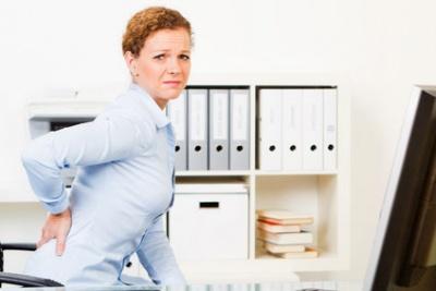 Женщина страдает от боли в спине